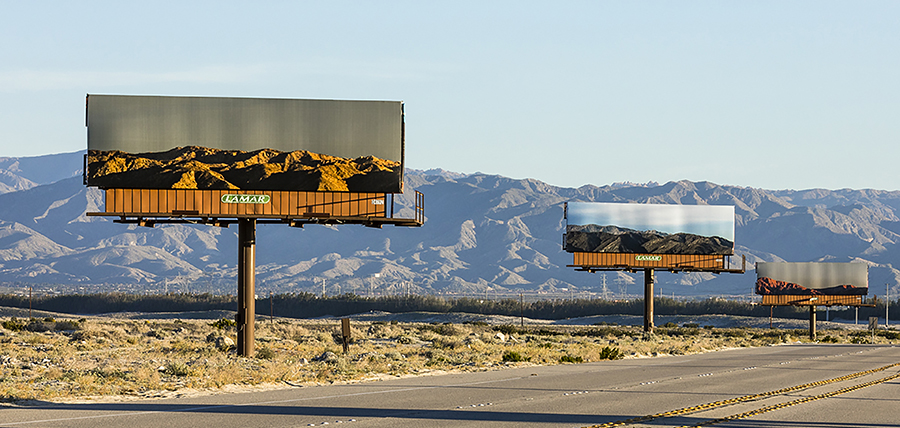 Photograph of a road with mountains in the distance. The road is lined with three large billboards depicting photos of those same mountains at different times of day.