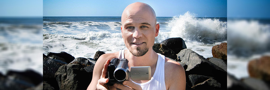 Photo of Adam Kamil holding a video camera with the ocean behind him.