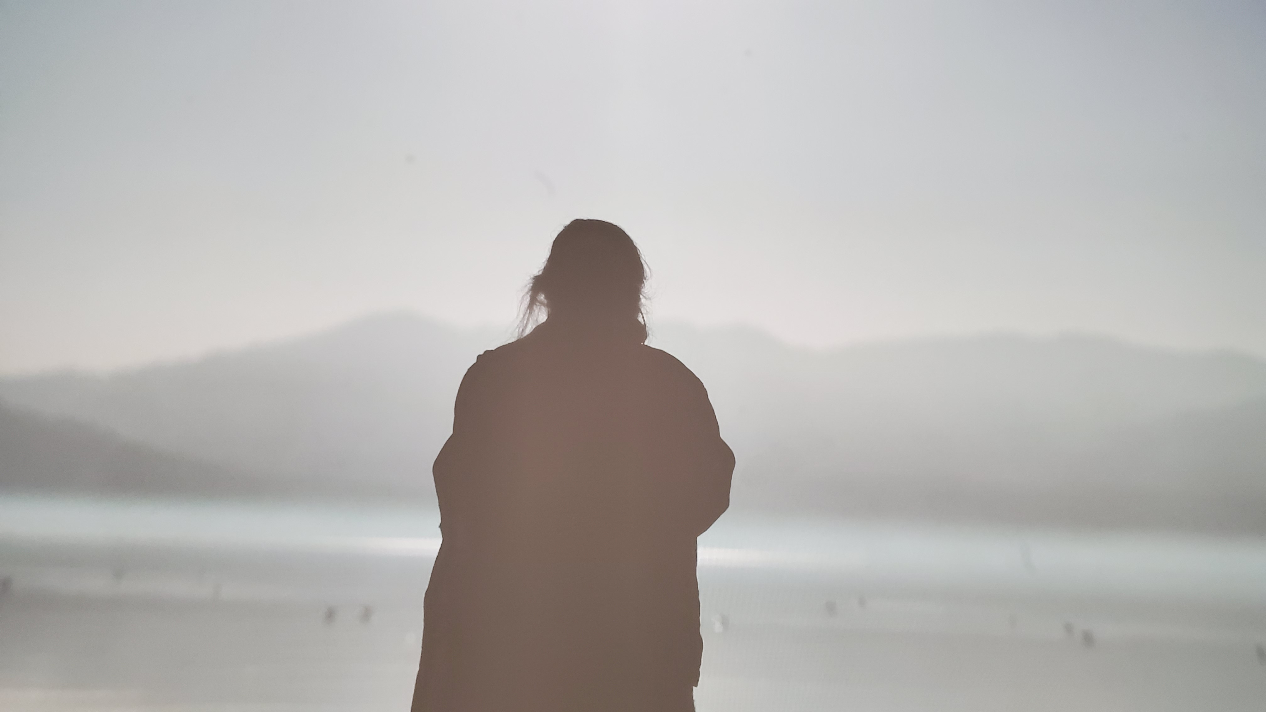 Photo of Heige Kim in silhouette standing on a plain or seashore with mountains in distance